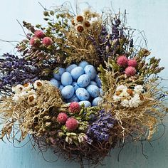 "This lovely Easter nest is crafted from California-grown oak moss, lavender, pink globes, white ammobium and Santa Cruz oregano, and filled with 24 truffle ""robin's eggs"".  Williams-Sonoma"