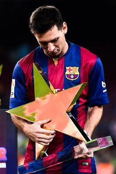 Lionel Messi of FC Barcelona holds the MVP trophy at the end of the Joan Gamper Trophy match between FC Barcelona and Club Leon at Camp Nou on August 18, 2014 in Barcelona, Catalonia.