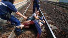 Eine Mutter versucht ihr Kind zu schützen, als die Situation eskaliert und die Polizei handgreiflich wird. Ungarische Polizeibeamte hatten einen Zug Richtung Westen geräumt.
