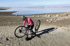 Monica Soares fixes the chain on her bicycle on part of the dry lake bed at Folsom Lake near Folsom, Calif., Thursday Jan. 9, 2014.