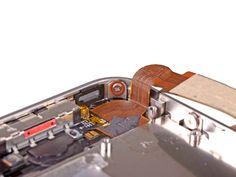 5. Retire el tornillo de 1,5 mm Phillips cerca del cable conector dock.