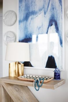Modern wood table with a gold lamp, small ceramic accessories