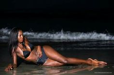 NIKKI DAVIS GORGEOUS DARK SKINNED WOMAN AND SHE IS WEARING  A BLACK BIKINI AND A BLACK BACK TIE UP AND NECK TIE UP  TOP AND SHE IS AT THE  BEACH LAYING IN THE LOW TIDES OF  THE WATER