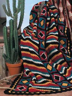 """Bold colors accented with black create this striking traditional diamond and striped pattern. Afghan is worked in panels using worsted weight yarn and a size G/6 crochet hook. Size: 43 1/2"""" x 65 1/2"""".Skill Level: Advanced"""