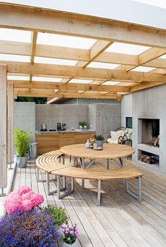 Utestue med betongpeis og betongvegger, rundt bord i treverk og utekjøkken