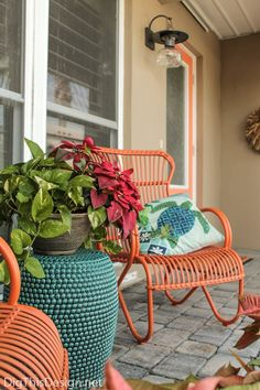 Orange metal rocking chairs in the front porch and matching orange door.