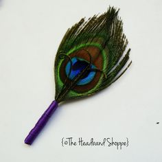 Peacock feather boutonniere: this new design is for the frugal bride - at a lower price point, you will receive a simple feather boutonniere...    ...1 natural brilliant peacock feather trimmed and wrapped with a purple satin base. A spray of curled bronzy gold wisps finish it off. Alternate base colors available upon request.    Unlike our other designs, this is a simple standard boutonniere to be affixed with a corsage/bout pin (included).    Measures 3.5 from base to main peacock feat...