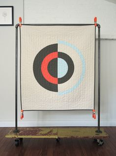 Graphic but minimal art/wall quilt or baby blanket. Concentric rings in various widths and off set colors: Sky Blue, Slate and Coral on Ivory approx