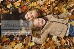 Portrait of Girls Lying Down in Autumn Leaves