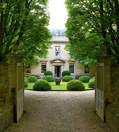 Inspiration for entry circle. Architectural Digest article on Cole Park, owned and designed by Anouska Hempel, formal entry garden framing Georgian historic home, circle punctuated with boxwood mounds.