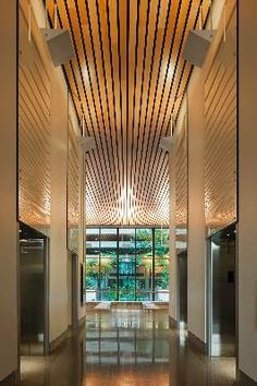 The elevator bank in the main lobby of the Edith Green-Wendell Wyatt Federal Building in Portland, Oregon, uses light colored lumber and polished finishes to bring daylight into the area. Photo credit: Nic Lehoux Architectural Photography.