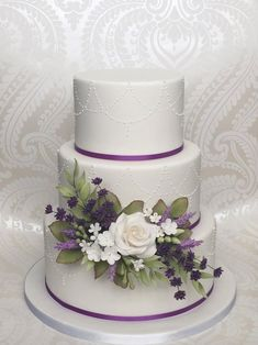 3 tier white and purple wedding cake with delicate piping details. Decorated with a small cascade of sugar roses, purple lavender and various types of sugar foliage. Wedding Cake Base, 3 Tier Wedding Cakes, Wedding Cake Prices, Small Wedding Cakes, Purple Wedding Cakes, Wedding Cakes With Flowers, Wedding Cake Designs, Our Wedding Day, Wedding Stuff