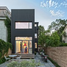 the previously long, narrow home has been opened up on all levels, with the rear portion of the dwelling clad with black vertical boards to attract the sun\'s rays.
