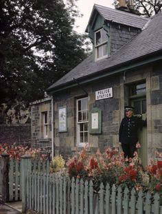 'Policeman and dog stand at police station door in flower garden.' by National Geographic