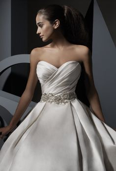 Brides: Private Collection by Alfred Angelo. Satin gown with wrapped sweetheart bodice cinched with a beautiful band of rhinestones, crystal beads and pearls that lead to a box-pleated full skirt. Comes with optional spaghetti straps, side pockets and features covered buttons down the chapel train.