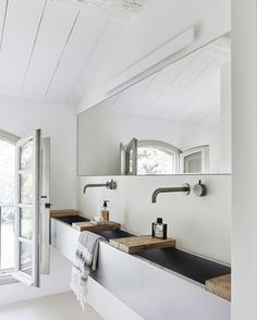 White modern bath with an elongated trough sink, creatively separated by reclaimed blocks, paired with high faucets.