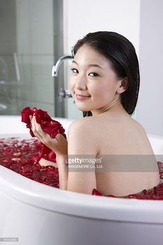 Young woman having the bath with roseleaves and looking at the camera : Stock…