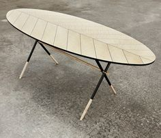 Piuma Table  Oval table with intarsia in Curly Maple and pattern of a bird feather. Tubular iron legs painted in black with ends and crosspieces in solid Maple. Legs joints and feet elements in brushed brass.