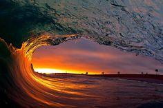 Clark Little, photographe surfeur hawaïen, réalise ses photos à l'intérieur des vagues. Ici lors d'un coucher de soleil à Newport Beach, Californie. ©  Clark Little