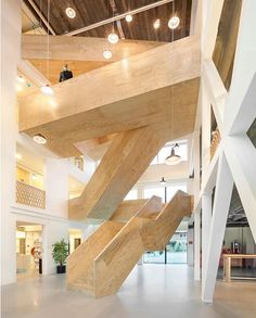 A 14-meter-tall void houses a giant sculptural staircase with timber steps at #studioninedots' De Burgemeester office complex, providing a communal space with shared amenities for its numerous tenants. 📸: Peter Cuypers. #architecture #interior #design #interiordesign #staircase #office #netherlands