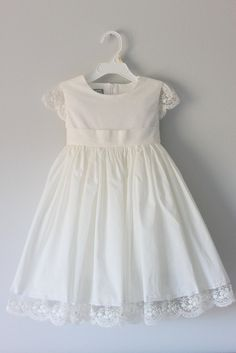 Dress color: White or Off-White (Dress shown in off-white) Lace cap sleeves Lace hem 100% Swiss cotton voile Fitted bodice Full skirt Sash at the