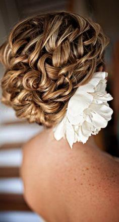 Hermoso recogido acompañado de un tocado de flor blanca.