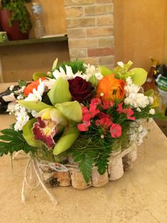 cinesini orchidee ranuncoli e rametti di betulla alla  vase