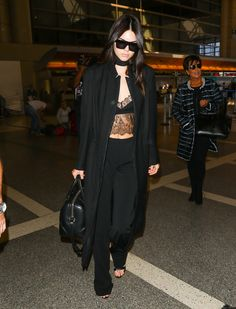 Looking nothing short of a '90s supermodel, Jenner dons a thick black choker, lacey bra top, long jacket, and high-waised black trousers in the airport.   - MarieClaire.com