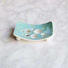 Handgemachte Keramik-Porzellan-Seifenschale mit einem Aqua Glasur und Blase Löchern.  Gebogene Form, die meisten Seifen zu halten. Türkis / Aqua glänzende Glasur. Löcher um die Seife abfließen zu lassen. Porzellan-Kugelfüßen. Seife Teller ca. 80 mm x 104 mm  Bitte leichte Unterschiede in der Glasur durch die handgemachte Prozesse ermöglichen. Ihnen wird genau so schön wie den hier gezeigten sein.  Als Grafik-Designer bin ich zu entwerfen Logos mit minimalen Details und maximale Wirkung v...