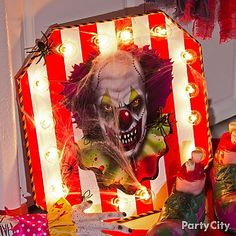 DIY your own mad clown marquee! Cut poster board into an octagon & create circus stripes with red & white duct tape. Then, poke through the globes from string lights & secure the globes with hot glue. Finish by attaching a clown face, spiders & cobwebs!