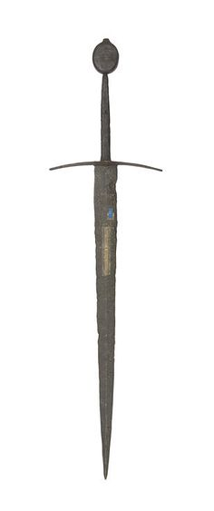 A Medieval Sword Of Oakeshott Type XVIII Circa 1400 In excavated condition, with broad sharply tapering blade of flattened diamond section, the hilt comprising slightly arched tapering quillons of triangular section flat along the top and thickening to form a shallow ridged projection over each face of the forte, flat tapering tang with rounded edges, and large flat circular pommel drawn-out at the top to form a button