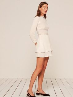 A little romance. This is a long sleeve, mini length dress with lace trim detail and a high neck.