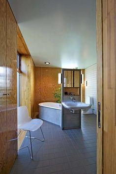 SAMSPILL. Fra soverommet er det lett atkomst til badet. Badekaret står på en røff betongsokkel.