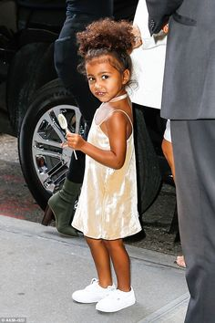 Strike a pose: North seemed most interested in her lollipop...