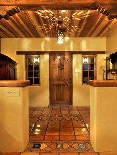 Talavera tiles, popular in Mexico due to the availability of fine clays, adorn this yellow entryway. Designers Wayne and Kiki Suggs of Classic New Mexico Homes added decorative tin lighting to achieve a whimsical look in this pueblo revival home.