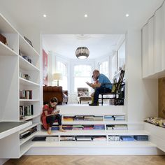 Books can be stored beneath the wide steps of this staircase that connects the two halves of a split-level living room inside a renovated London flat