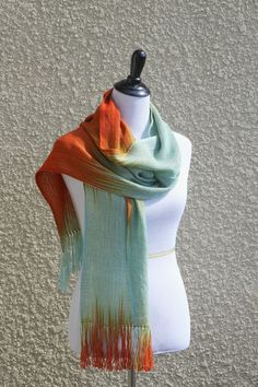 Hand woven long scarf made in pooling technique. This means that color is gradually changes from blue to orange and red colors. Also there is a thin tencel thread in golden color which adds a luxury l