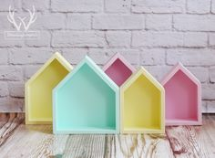 Stylish sets of house-shaped shelves in trendy colors.