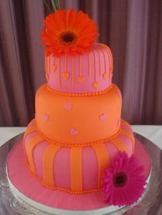 Orange and pink three tier wedding cake decorated with pink daisies