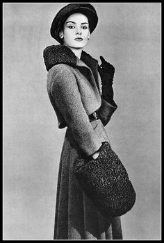 Model in dark green tweed suit, short jacket has large astrakhan collar to reveal black leather belt, worn with pleated skirt, by Pierre Balmain, photo by Georges Saad, 1956
