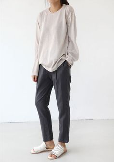 taupe long sleeve shirt, grey trousers, white sandals