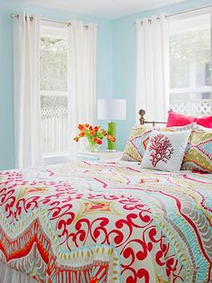 One of the easiest ways to get a colorful bedroom is to start with colorful bedding and build your color scheme from there. Pull out one color for the walls and other colors for accessories, but don't feel like you need to color everything. Here, billowy, white curtains ensure the bright bedroom is still livable.