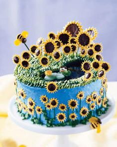 Sunflower Pond Cake: 1 box Duncan Hines Classic yellow cake mix (1 lb, 2.25 oz) prepared as directed for poundcake  2 cans (16 oz each) vanilla frosting  Yellow, blue and green paste (icing) food color*  1 box (5.5 oz) Junior Mints  4 chocolate-covered mint patties (about 1-1/2 in. across)  1 chocolate-coated cookie (about 1-3/4 in. across)  1/4 cup each mini and regular brown M's  2 boxes (3 oz each) Jell-O Berry Blue gelatin  Yellow Fruit by the Foot  White and red tube frosting  1 green…