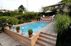 Une piscine semi-enterrée, avec un coin détente au fond et des herbes tout autour.