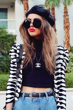 Black cropped tee, black/white graphic pattered jacket with puffy shoulders, high-waisted blue jeans, Chanel necklace