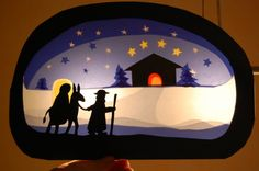 Holiday Waldorf silhouette. Need dark card stock, craft knife, craft cutting board, different colors of tissue paper, glue, tape, and light from a window or candle.