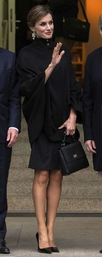 Doña Letizia arrived at the museum wearing a new cape swing coat and a little black dress, that dates back to 2011, both from Hugo Boss. Doña Letizia dressed in an amazing high-collar, cape-shaped black topper and called attention to the button details on her neckline with her hair pulled up in a bun and shiny drop earrings. Museum Kunstpalast, Düsseldorf, 09.10.2015.
