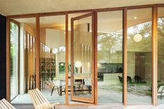An outside deck can be accessed via floor to ceiling doors. Timber Cabin, Timber Structure, Minimal Home, Sustainable Architecture, Contemporary Architecture, Architect Design, Large Windows, Prefab, Concrete Floors