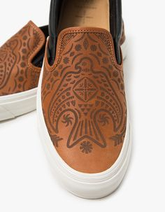 From Vault by Vans in collaboration with Brooks England, the classic Slip-On shoe in Tortoise Shell. Laser-etched artwork from Taka Hayashi. Elasticized tongue gussets. Padded collar. Vans branded flag tag. Crushed leather cushioned heel liner.