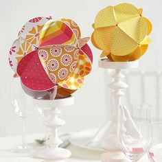 Easy cut-and-fold shapes combine to make cheerful dimensional spheres. Use patterned and solid paper in your wedding colors for a fun, fresh look. These would be a super cute ornament centerpiece around the holidays with green or red paper.